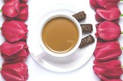 La taza del café con leche se coloca en una placa blanca con el fondo blanco cerca de tulipanes multicolores foto de archivo libre de regalías