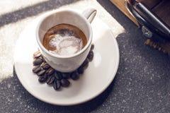 La taza del café express, el grano de café, el canela y las flores secadas sacuden en de madera Fotos de archivo