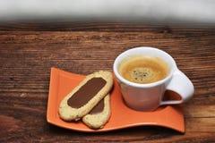La taza del coffe y poca galleta en una tabla de madera rústica Fotos de archivo libres de regalías