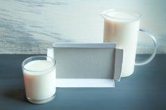 La taza del jarro y del vidrio con la almendra ordeña en la tabla de madera Intolerancia sin lactosa foto de archivo