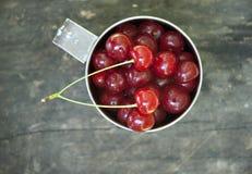 La taza del metal llenada de las cerezas Fotos de archivo libres de regalías