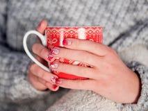 La taza del ` s del Año Nuevo en manos femeninas con Año Nuevo hermoso manicures imagenes de archivo