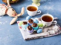 La taza dulce de Pascua apelmaza treets en cáscaras de huevo coloridas en azul fotos de archivo libres de regalías