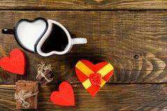 La taza en la forma de corazones, una vertió el café en la otra leche, después la guita tajada del chocolate atada alrededor del  Imagen de archivo libre de regalías