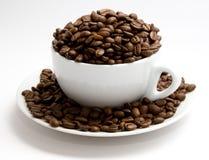 La taza llenó de los granos de café imagenes de archivo