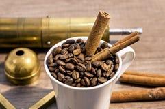 La taza llenó de los granos de café, de la amoladora, del turco y del canela en la tabla de madera Foto de archivo libre de regalías
