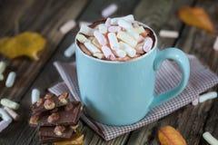 La taza llenó del chocolate caliente y de la melcocha, con el chocolate Foto de archivo
