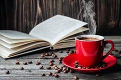 La taza roja de café y de libros abrió el diario en la tabla de madera con los granos de café imagenes de archivo