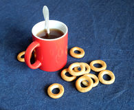 La taza roja de té negro y las sequedades están en el primer de la tabla Foto de archivo libre de regalías