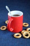 La taza roja de té negro y las sequedades están en el primer de la tabla Fotos de archivo