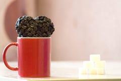 La taza roja se coloca en la tabla, cerca de la taza la forma de los granos de caf?, un s?mbolo del coraz?n del amor foto de archivo libre de regalías