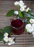 La taza transparente de bebida roja adornada con una flor Imágenes de archivo libres de regalías