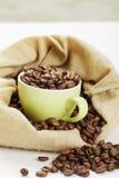 La taza verde llenó de los granos de café en bolso Imagen de archivo libre de regalías