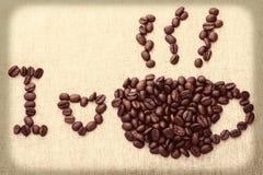 La taza y el humo de café forman por los granos de café Imagen de archivo libre de regalías