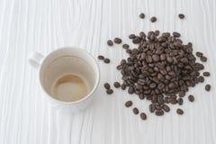 La taza y las habas de café con las manchas del café no han lavado la taza colocada en la tabla blanca Fotos de archivo