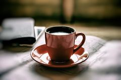 La tazza arancio di caffè caldo preparato fresco sta sui disegni e su una s Fotografia Stock