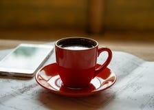 La tazza arancio di caffè caldo preparato fresco sta sui disegni e su una s Immagini Stock Libere da Diritti