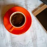 La tazza arancio di caffè caldo preparato fresco sta sui disegni e su una s Fotografia Stock Libera da Diritti