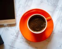 La tazza arancio di caffè caldo preparato fresco sta sui disegni e su una s Fotografie Stock