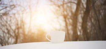La tazza bianca sta sulla neve Immagine Stock