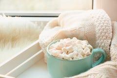 La tazza blu di cioccolata calda con la caramella gommosa e molle sul davanzale con la pelle da pellicceria per si rilassa Concet Fotografia Stock Libera da Diritti