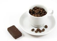 La tazza con i chicchi ed il cioccolato di caffè ha isolato immagine stock