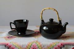 La tazza con il piattino e la teiera sono sulla tavola Immagine Stock