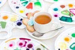 La tazza con tè ed il biscotto ha circondato la tavolozza dell'acquerello Immagini Stock