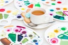 La tazza con tè ed il biscotto ha circondato la tavolozza dell'acquerello Fotografia Stock