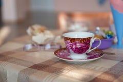 La tazza d'annata della porcellana con il piattino per tè sta su una tavola coperta di tovaglia appuntita fotografia stock libera da diritti
