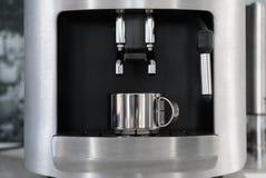 La tazza d'argento del metallo è nella macchina di caffè espresso Immagini Stock Libere da Diritti