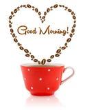 La tazza da caffè con i chicchi di caffè ha modellato il cuore con il segno di buongiorno Fotografia Stock