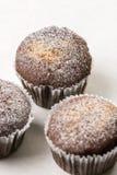 La tazza dei brownie del cioccolato agglutina con lo zucchero in polvere sui precedenti di marmo bianchi Immagine Stock
