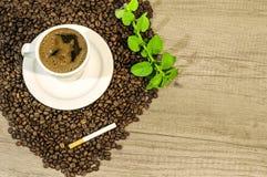 La tazza del tè fresco del caffè, dei chicchi di caffè, del sigaro e della menta fiorisce sulla tavola Immagini Stock