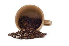 La tazza di Brown con i fagioli di cofee ha versato da esso immagini stock