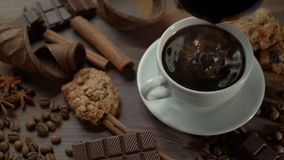 La tazza di caffè caldo con i bastoni di cannella, le fette del cioccolato e l'anice star sulla vecchia tavola di legno stock footage
