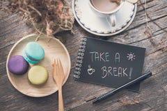 La tazza di caffè con il maccherone e prende una nota della rottura Fotografie Stock Libere da Diritti