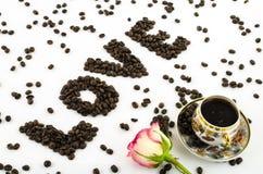 La tazza di caffè della porcellana con i chicchi rosa di caffè e del fiore ama Fotografia Stock