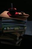 La tazza di caffè ed i biscotti ed il cioccolato sulla pila di libri Fotografia Stock