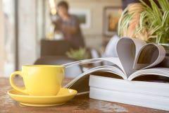 La tazza di caffè gialla che dispone insieme alla rivista gradisce la forma del cuore fotografia stock