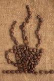 La tazza di caffè ha prodotto i chicchi di caffè del ââof su una tela da imballaggio Fotografia Stock