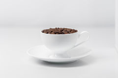 La tazza di caffè ha riempito di chicchi di caffè Fotografie Stock