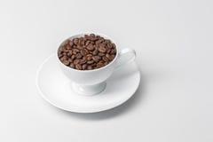 La tazza di caffè ha riempito di chicchi di caffè immagine stock libera da diritti
