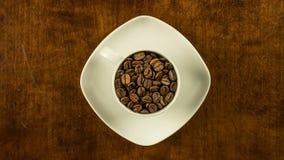 La tazza di caffè ha riempito di fagioli ferma l'animazione di moto che gira il topview in senso orario video d archivio
