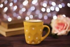La tazza di caffè, il tè, vecchi libri ed è aumentato sulla tavola di legno in caffè con il fondo della luce del bokeh Concetto d fotografie stock