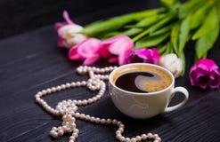 La tazza di caffè, la collana della perla ed il mazzo dei tulipani sul nero corteggiano Fotografia Stock