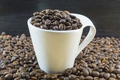 La tazza di caffè macchiato ha riempito di chicchi di caffè disposti su coff arrostito Immagine Stock