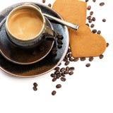 La tazza di caffè nero con cuore ha modellato i dolci su bianco Fotografia Stock