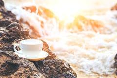 La tazza di caffè sulla pietra nella spiaggia e l'acqua spruzzano fotografia stock libera da diritti