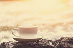 La tazza di caffè sulla pietra nella spiaggia e l'acqua spruzzano fotografia stock